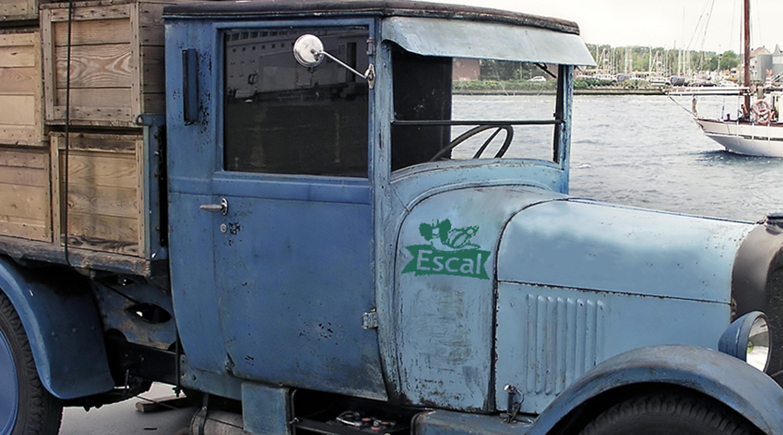 Un vieux camion bleu avec le logo d'Escal