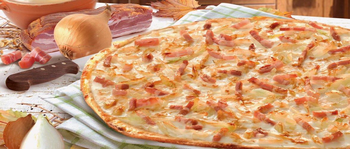 Ein Flammkuchen nach Elsässer Art auf einem grün weiß karierten Tuch dekoriert mit einer Zwiebel, einem Messer, einer Schüssel mit Creme und einer großen Speckscheibe