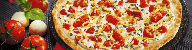Une tarte fine avec des tomates, du basilic et du mozzarella