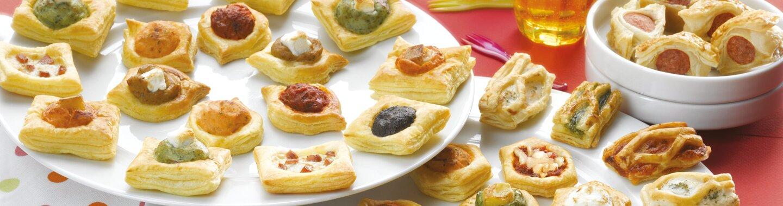Viele verschiedene Blätterteighäppchen auf Tellern und in Schüsseln angerichtet