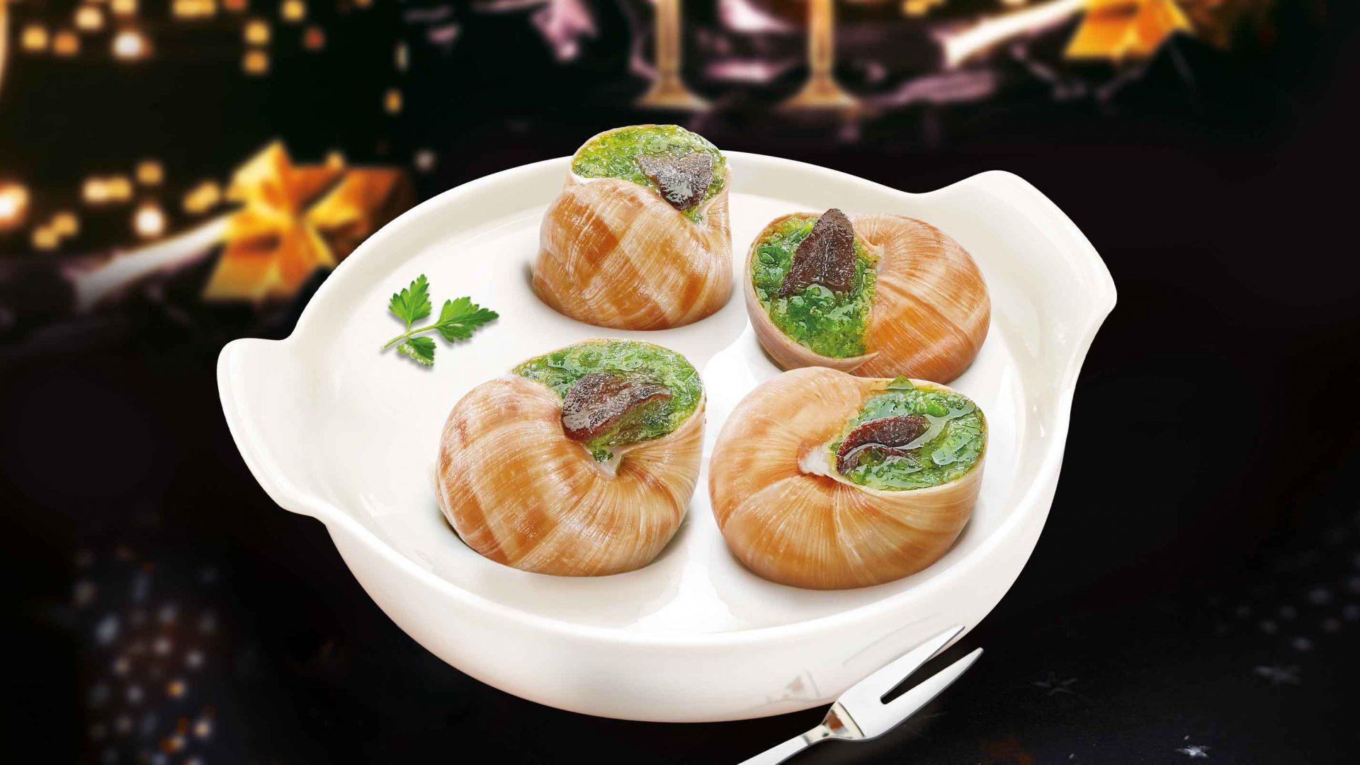 Une assiette blanche avec 4 escargots de Bourgogne avec un arrière-plan festif